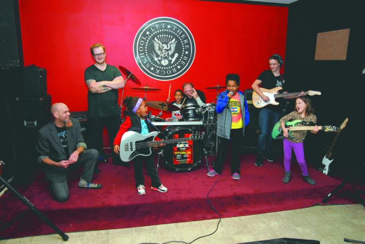 Journal photo by Jeff McCoy Let There Be Rock School owner Butch Rice smiles as his students take the stage. Pictured from left are Rice; Nick Lemley, guitar instructor and band manager; Frara Rice; Donte Ware, drummer; Brian Appell, drum instructor; Liliana Rice, Noah Ziegler and Ella Beach. The kids will play their first concert Sunday at 2 p.m. at the Blue Fox in Winchester, Va.