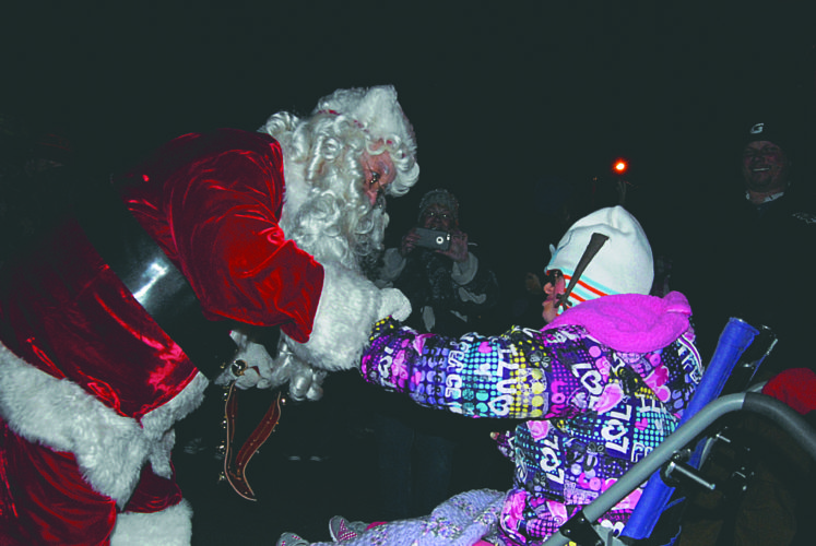 (Journal photo by Jeff McCoy) Santa Claus greets Katie Belaportas on Friday at Hedgesville's official Christmas tree lighting ceremony.