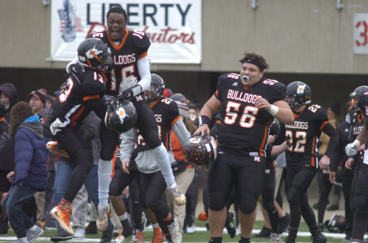 Martinsburg's Kionte Cook (13), Michael Boaitey (16) and Trey Henry (56) celebrate after the Bulldogs' 49-7 victory over Spring Valley in the Class AAA title game. It was Martinsburg's fifth state championship.