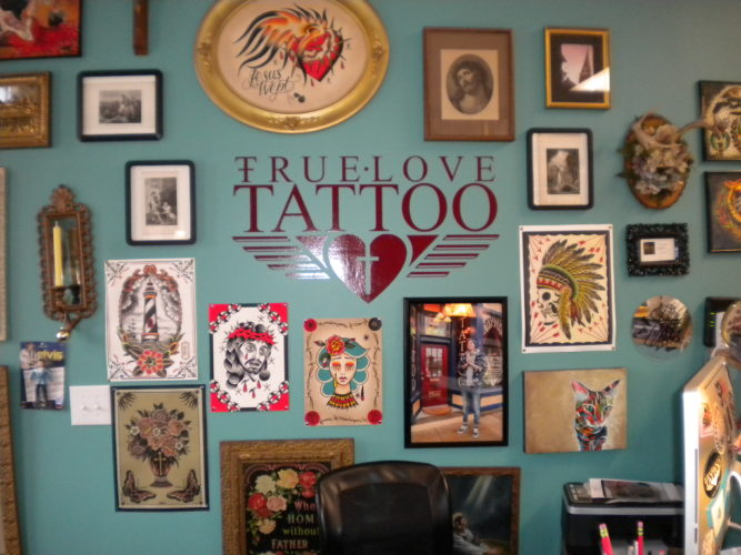 (Photos by Sasha Braithwaite) A wall decorated with artwork and the shop's logo is shown inside of True Love Tattoo Parlor, located at 119 E. Martin St., recently in Martinsburg.