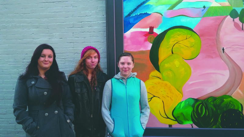 (Journal photo by Danyel VanReenen) Washington High School students, from left, Lauren Scuka, Agnes McAuliffe and Kailee Bal stand beside the mural of Charles Town on Saturday the threesome created on the outside wall of Collin's Barbershop in Charles Town.