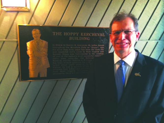 (Journal photo by Matt Dellinger) Hoppy Kercheval stands beside a new plaque Wednesday dedicating the WEPM building in Martinsburg in his honor.