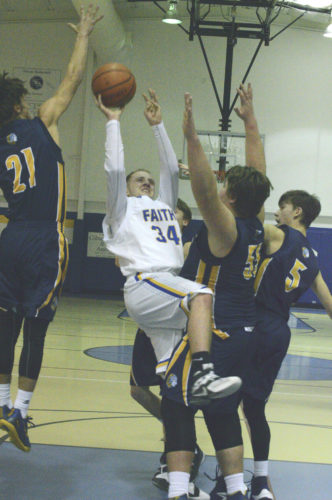 Faith Christian's Brady Mann drives to the basket through Berkeley Springs defenders during Thursday's game.