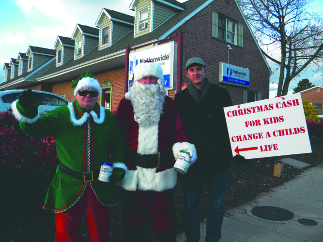 "(Journal photo by Jim McConville) Santa Claus and his main elf ""Sparky,"" along with Nationwide agency owner Cody Eckenrode, collect funds for Christmas Cash for Kids on Friday in Martinsburg."