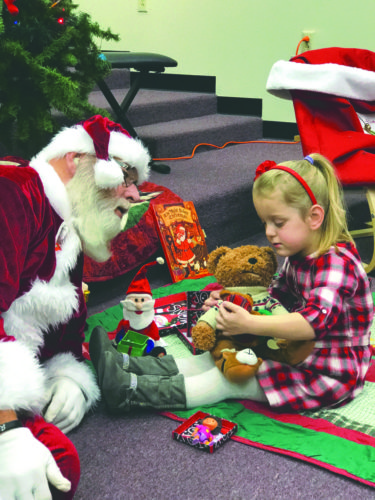 Submitted photo A sensory friendly version of Santa Claus interacts with Payton Crowe on Saturday at Tomahawk Intermediate School.