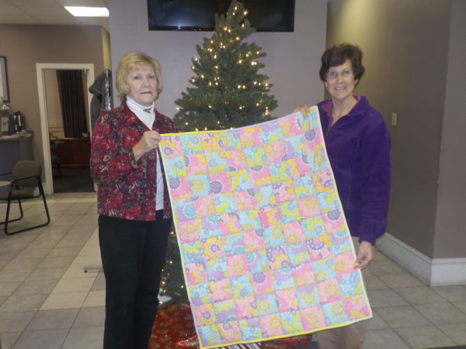 Submitted photo As part of the 'Santa to a Senior' program, Donna Frye, left, presents a handmade quilt that she made to Lisa Jacque, right, coordinator for Home Instead.