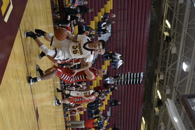 Photo by David Pennock Jefferson's Will Fields dribbles past a Sherando defender during Saturday's championship game of the Cougar Classic basketball tournament.