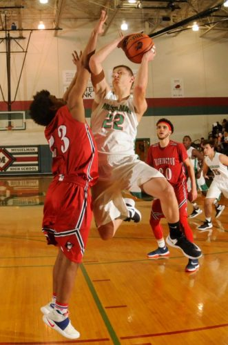 Musselman's Devon Caton, center, goes up for a shot as Washington's Trajon Brown defends during the third quarter on Wednesday in Inwood. See more photos on CU.journal-news.net.  (Journal photo by Ron Agnir)
