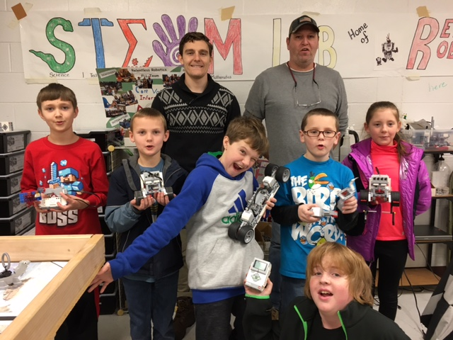 (Submitted photo) Pictured here with their Tuesday robot builds are Levi Hott (front), Malachi Unger, Joshua Walls, Chago Ellis, Robert Stevens, Georgia Powell, with Zach White (Johns Hopkins Civil Engineer graduate), Keith Young, (Robot Coach), and not pictured Lyric Loving, Brody Beal, Randy Young, Isaac Hott, and Coach Ken Craft.