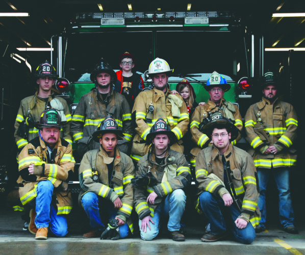 Journal photo by Jeff McCoy Kneeling, from left, are Mickey Tumblin, Jonathan Rodriguez, Garrison Huggins, Marc Huyett. Standing are Cody Kief, Brett Hutchinson, Burroughs' son Izaac Gilbert, Chief P.J. Burroughs, Burroughs' daughter Emery Burroughs, Lt. Brian Golliday and Dirick McDonald at the South Berkeley Volunteer Fire Department awaiting the bell for the next call.