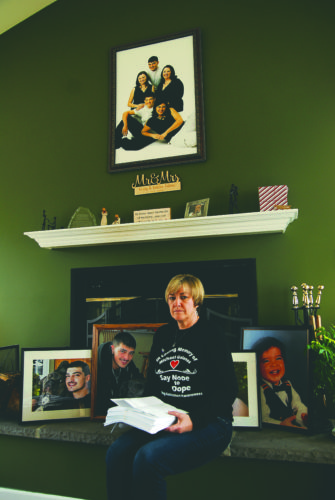 (Journal photo by Jeff McCoy) Grieving mother Colleen Collins sits in front of photos of her son as she holds a stack of emails and social media post printouts that were sent to her since her son Michael Galanos passed away from an overdose. Collins is reaching out sharing her tragic story in hopes that other families will not go through it.