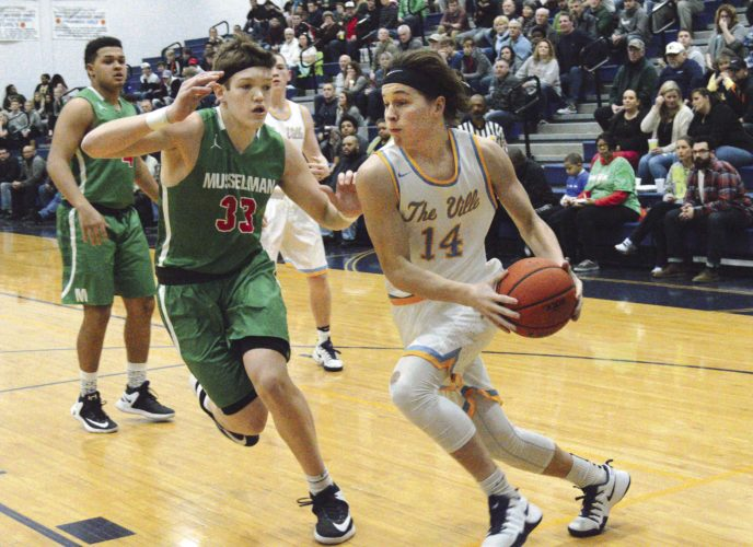 Hedgesville's Breck Gates, right, drives under the basket as Musselman's Jake Stephens defends during their game Friday at Hedgesville.