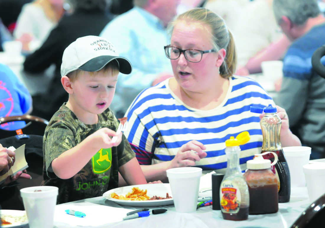 Journal photos by Ron Agnir Connor Craze, 3 1/2, and Tiffany Craze, Charles Town residents, munch on some pancakes and sausages at the Citizen's Fire Company Pancake Day on Tuesday afternoon in Charles Town. It's the 57th year for the event they estimate feeing over 2,000 people.
