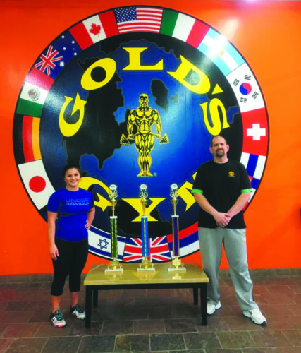 Megan Short, left, poses with her power lifting trophies along with coach Mike Powers. Short, who recently participated in her first competition, is taking the power lifting world by storm.