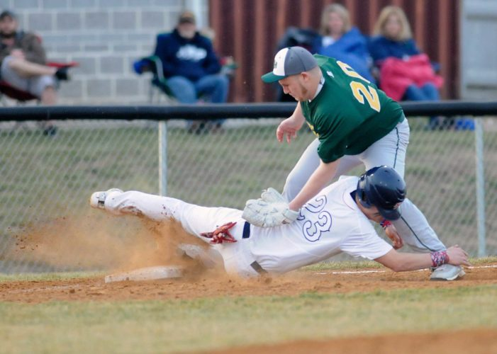 Spring Mills' Braden Stutzman (23) slides into third base ahead of the tag of East Hardy's Nick Miller (20) during the second inning Tuesday evening in Martinsburg. See more photos on CU.journal-news.net. (Journal photo by Ron Agnir)
