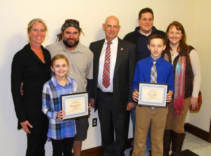 2017 agriculture poster contest winners and their families pose with Commissioner of Agriculture Kent A. Leonhardt in his office during Ag and Conservation Day at the Legislature. Pictured, from left, are Betsy, Marley and Damian Heath of Morgan County, Commissioner Leonhardt, and Mark, Micah and Shana Allen of Randolph County. (Submitted photo)
