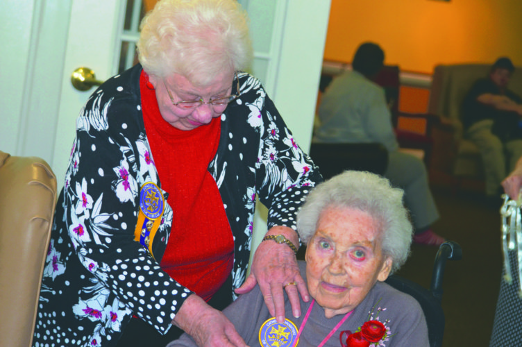 Meta Foster pins an award on Rosa-Lee Foreman on Wednesday, honoring Foreman for her contribution to the Catholic Daughters. (Journal photo by Adranisha Stephens)