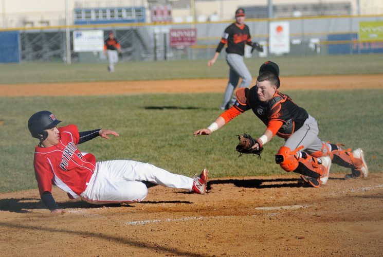 Washington baserunner Xavian Nawaz, left, slides home safely under the diving tag effot by Martinsburg catcher David Conner during the second inning in Charles Town Wednesday afternoon. See more photos on CU.journal-news.net. (Journal photo by Ron Agnir)