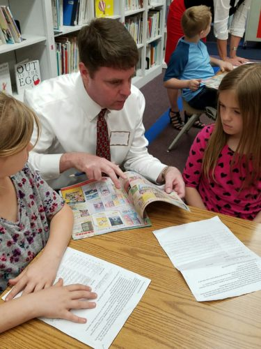 David Dalton, volunteer with Berkeley County Schools, collaborates with students during a recent book fair. (Submitted photo)