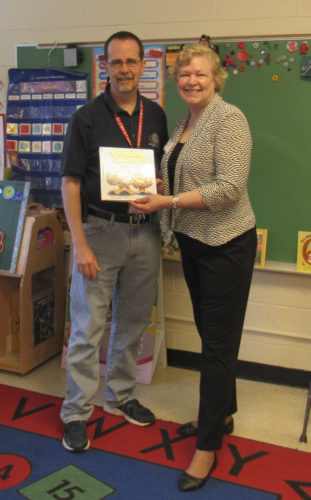 Judith Van Tol Wilson presents a copy of her book to principal Scott Jacobson. (Submitted photo)
