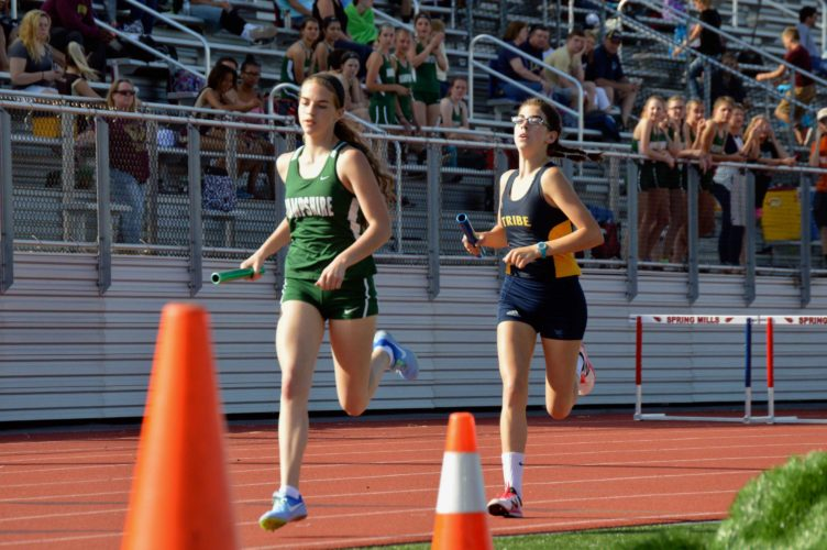 Journal photo by Jessica Manuel Berkeley Springs' Amanda Lupton, right, tries to make up ground on Hampshire during the 4x800 in Friday's Cardinal Classic track meet.