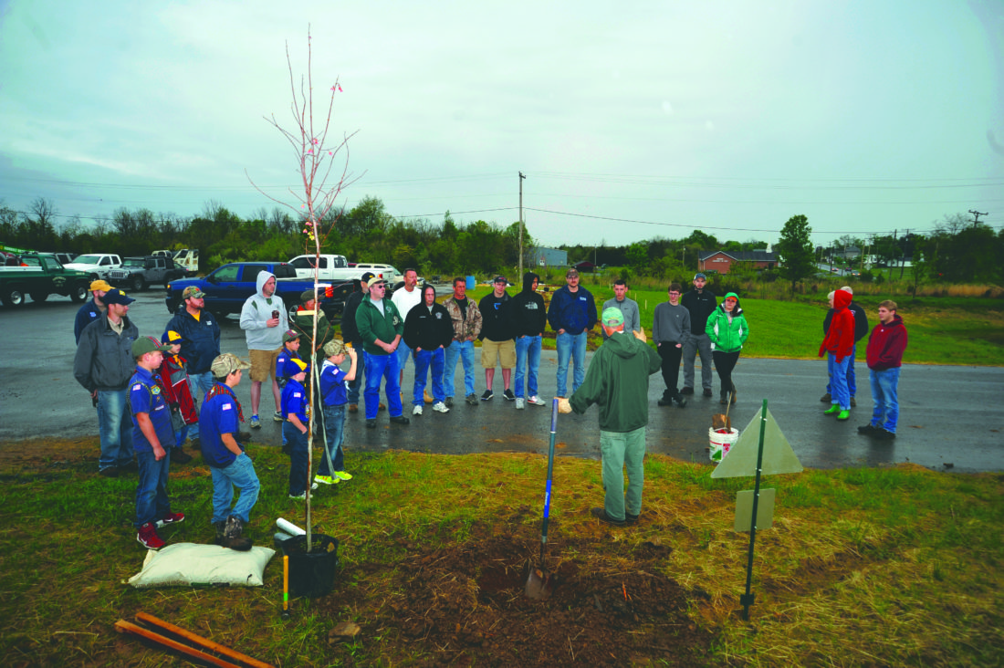 (Journal photo by Jeff McCoy) Forester Herb Peddicord, of the West Virginia Divison of Forestry, center, shows members of the public, along with South Berkeley Volunteer Fire Department and Cub Scout Pack 91, the proper ways to plant trees Saturday in Inwood.