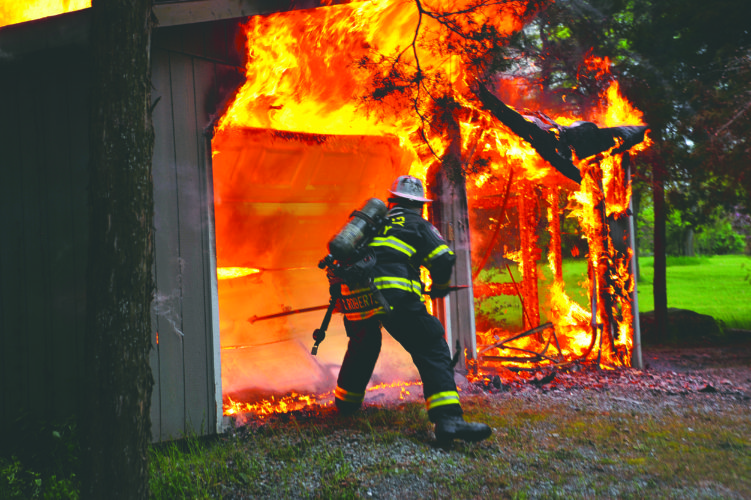 (Journal photo by Jeff McCoy) Assistant Fire Chief Cory Roberts, of Baker Heights Volunteer Fire Department, knocks down a garage door to make way for firefighters at a two-car garage at 63 Medmonton Road in Martinsburg.