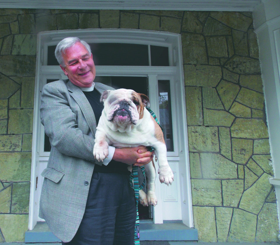 """Journal file photo by Ron Agnir The Rev. George T. """"GT""""Schramm holds his bulldog Eloise at his pastoral office in Shepherdstown."""