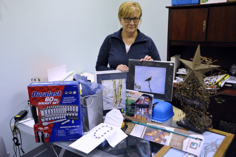 Good Samaritan Free Clinic Director Cobby Davis sorts a few of the prizes and items for a silent auction fundraiser to be held Saturday for the Good Samaritan Free Clinic. (Journal photo by Jeff McCoy)