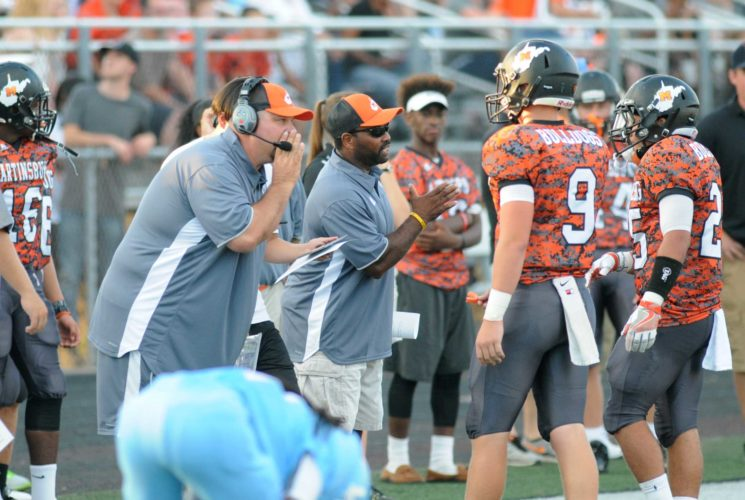 Martinsburg football coach David Walker whispers instructions to quarterback Tyson Bagent (9) and running back Mikey Jackson during the Buldogs' season-opener in 2016. Walker has been named the winner of the Van Meter Award as the High School Coach of the Year by the West Virginia Sports Writers Association. (Journal file photo by Ron Agnir)