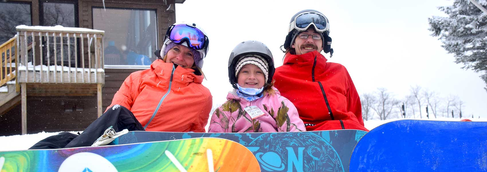family-of-snowboarders-sitting-on-snow-in-front-of-lodge