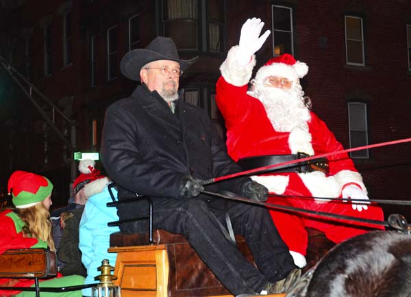 "Santa waves from a horse-drawn wagon during the annual Johstown ""Home for the Holidays"" Parade and Colonial Stroll on Main Street in Johnstown on Friday. (The Leader-Herald/Bill Trojan)"