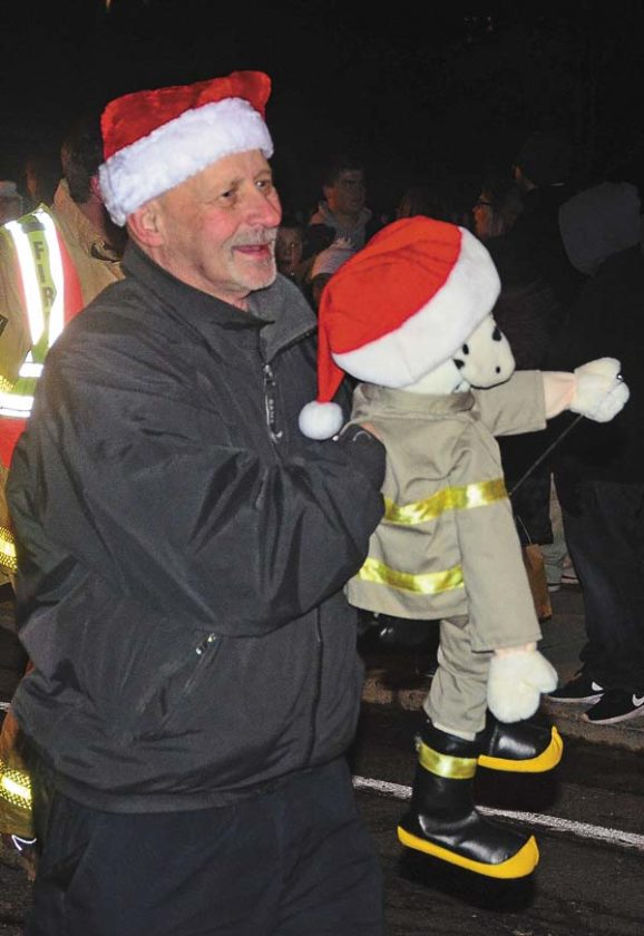 Perth Volunteer firefighter Edwin Leonard holds a fire dog puppet while participating in the annual Broadalbin Christmas Parade in the Village of Broadalbin on Nov.­ 28. (The Leader-Herald/Bill Trojan)