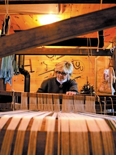 Eileen Wrightsman of Gloversville weaves on a 1779 barn frame loom during a demonstration during the annual Mayfield Hostorical Society's 25th annual Christmas open house at the Rice Homestead in Mayfield on Saturday. (The Leader-Herald/Bill Trojan)