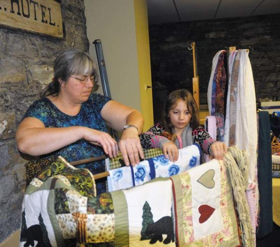 Wendy Mania, left, of Gemsewns of  Ephratah and her grandaughter, Kimberly Kirby of Fort Plain, place quilts on display at their booth for sale during the annual Fort Plain Christmas at the Fort at the Fort Plain Museum in Fort Plain on Saturday. (The Leader-Herald/Bill Trojan)