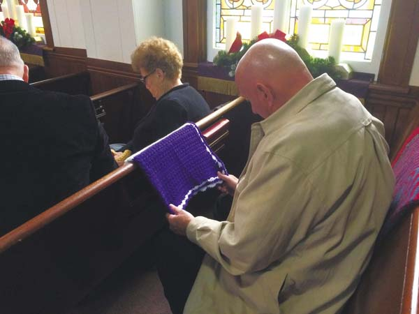 Pastor Jerry Oliver called the congregation together to help bless the lap robes before sending them to the veterans. (The Leader-Herald/Opal Jessica Bogdan)
