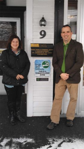 Enea Family Funeral Home recently adopted a tobacco-free policy in its St. Johnsville location that prohibits all tobacco use, including electronic smoking devices on its property. In this picture from Catholic Charities,  Community Engagement Coordinator Tricia Terleckey and Kevin Enea from Enea Family Funeral Home stand next to a tobacco-free sign. (Photo submitted)