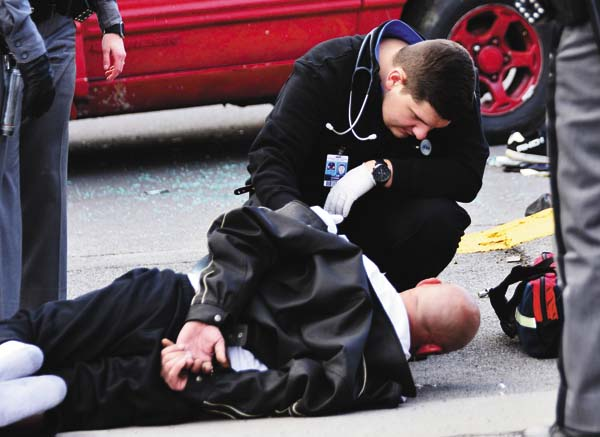 Paramedic Tyler Morris attends to Michael Urbanski on N. Perry Street in Johnstown Saturday after a police chase wound up with Urbanski's arrest. (The Leader-Herald/ Bill Trojan)