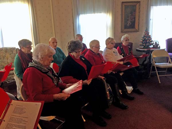 The Singing Seniors hold their song book, often containing more than 165 songs, as they bring Christmas spirit to others. (The Leader-Herald/Opal Jessica Bogdan)