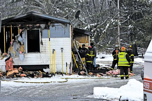 Firefighters and investigators work at the scene of a fatal mobile fire at 3786 State Hwy 30 in the town of Mayfield Wednesday.  (The Leader-Herald/Bill Trojan)