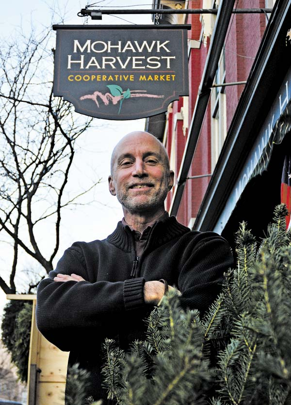 Chris Curro of the Mohawk Harvest places Christmas trees on display outside the business in Gloversville on Thursday. (The Leader-Herald/Bill Trojan)