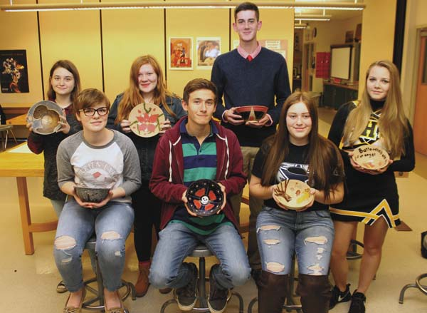Canajoharie High School students hold this bowls made for the Empty Bowls Project. Shown, from left, are  Skyler Hoffman, sophomore; Danyell Monk, junior; Felicity Folts,sophomore; Louis Hand,junior; Andrew Yacobucci, junior; Kiara Putnam, senior; and Bambi Consalvo, sophomore. Not pictured are Moira Rowe-Lilley and Hannah Smith. (Photo submitted)