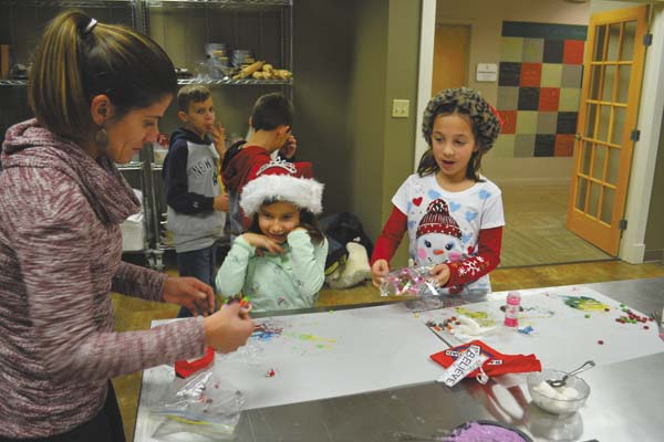 Melissa Maldonado of Mayfield helps her daughter, Nevaiah, 6, and her daughter's friend, Elaine Brown of Johnstown, in making cookies Saturday at The Polar Express celebration at the Paul Nigra Center for Creative Arts in Gloversville. (The Leader-Herald/Eric Retzlaff)
