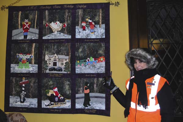 Linda Selbert stands next to a donated quilt bearing different displays and moments that can be seen through the light drive. Her own square is in the bottom right, modeled after her. (The Leader-Herald/Opal Jessica Bogdan)