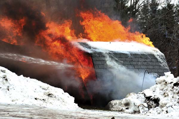 A storage garage for a local business goes up in flames before firefighters could knock it down. (The Leader-Herald/Bill Trojan)