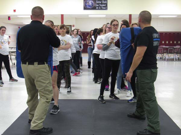 Amsterdam police officer Mike Malantine and officer Chris Cuddy stand at the ready as girls prepare to practice defense moves. (The Leader-Herald/Opal Jessica Bogdan)