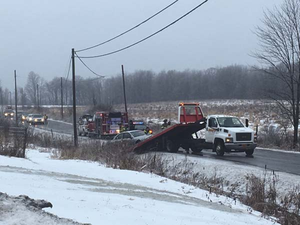 Firefighters, police and road workers remove a car from a ditch on County Highway 107 near Hales Mills. Fulton County Sargent Herbert Roots said the accident was caused by the car going too fast on the slick morning roads, He said the injuries were minor. (The Leader-Herald/Bill Trojan)