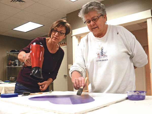Brenda Dwyer, Environmental and Creative Art Specialist at the Paul Nigra Center for Creative Arts, assists art student Donna VanAernam of Johnstown with her heart barn quilt Saturday during an art class at the center in Mayfield. (The Leader-Herald/Bill Trojan)