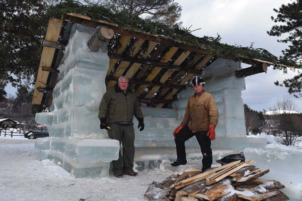 Brian McDonnell, left, and John Pietras, have built an ice lean-to near the Saranac Lake Winter Carnival Ice Palace. (Adirondack Daily Enterprise/Chris Knight)