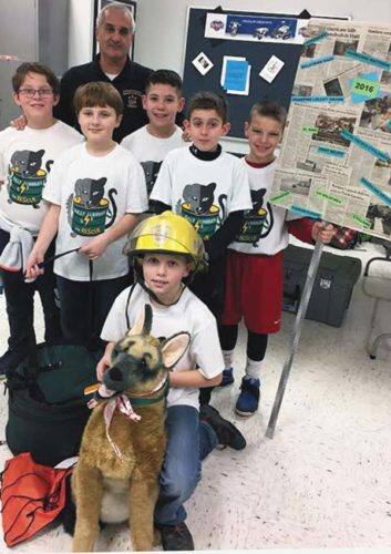 Fulton County Sheriff Richard Giardino meets with the the Broadalbin-Perth Intermediate School FIRST LEGO League Team-Fully Charged For Rescue!, standing from left, Ethan Waufle, Charles Santon, Giovanni Barboza, Jake Morin and William Ribar and, kneeling with stuffed dog, Owen Compani. (Photo submitted)